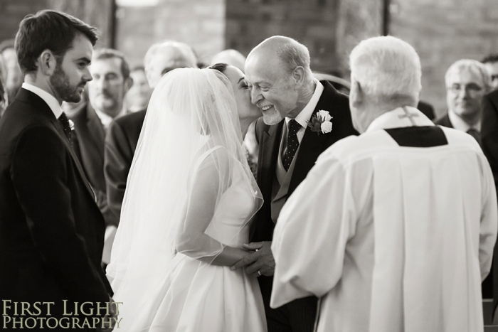 bride kissing father in church